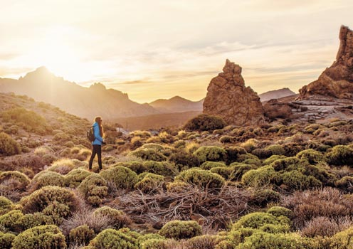 A woman walking through Teide National Park, Tenerife, at sunset