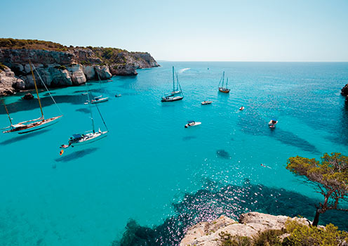 Boats on the clear blue waters of Cala Macarella, Minorca.