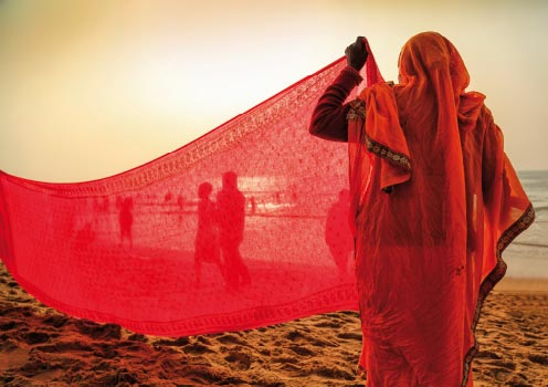 An Indian woman drying a colourful saree under the sun
