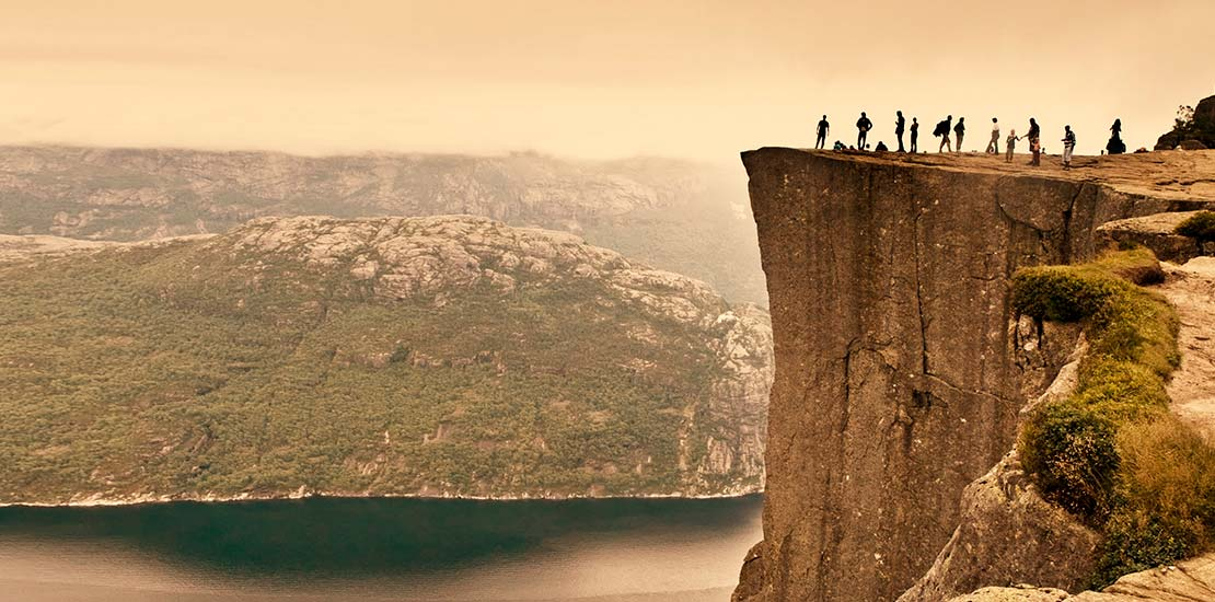 A group of people standing on the edge of Preikestolen cliff in Stavanger, Norway overlooking deep dark water.