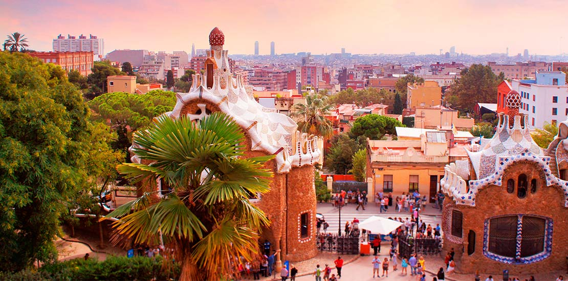 The city horizon of Barcelona, with palm trees and ornate white roofs, as seen from Park Guell.