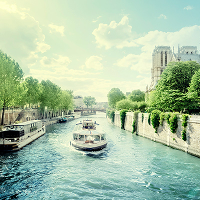A river boat cruises along a the blue Seine on a sunny day.