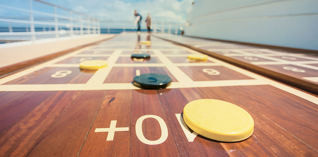 A couple taking part in a game of shuffleboard on deck aboard Saga Sapphire.