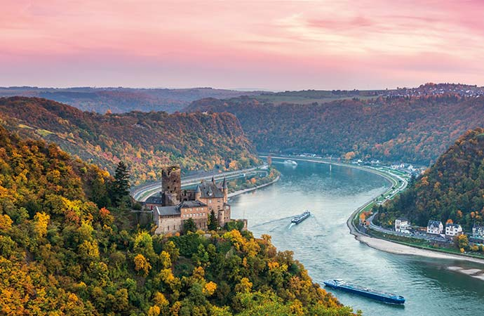 Katz Castle, above the town of Sankt Goarhausen, with the Rhine flowing past and a romantic sky as the sun sets behind the mountains.