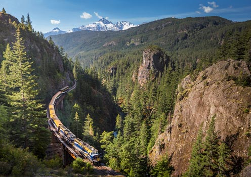 An aerial view of the Rocky Mountaineer passing through the mountainous landscape of Canada