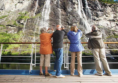 A group of tourists taking photos of a waterfall from the deck of a ship