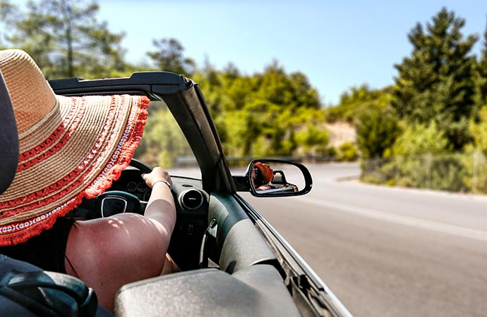 A woman in a straw hat driving along a road