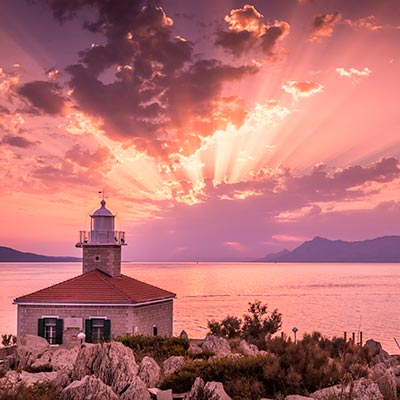The sun setting over a lighthouse in the Makarska Riviera