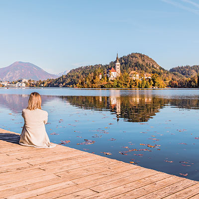 A woman sitting on a jetty admiring the castle at Lake Bled, Slovenia