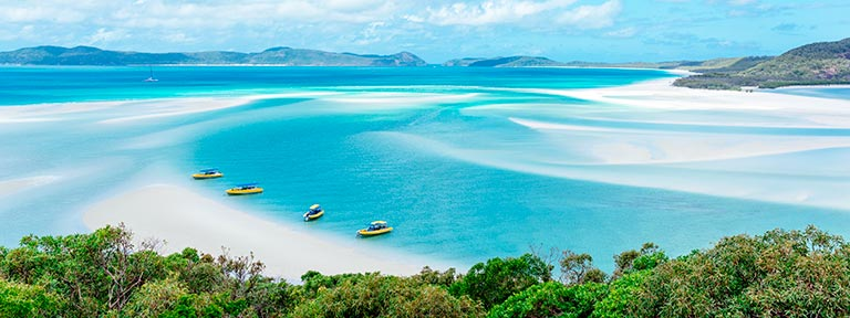 Boats moored along a stretch of Whitehaven Beach in Whitsunday